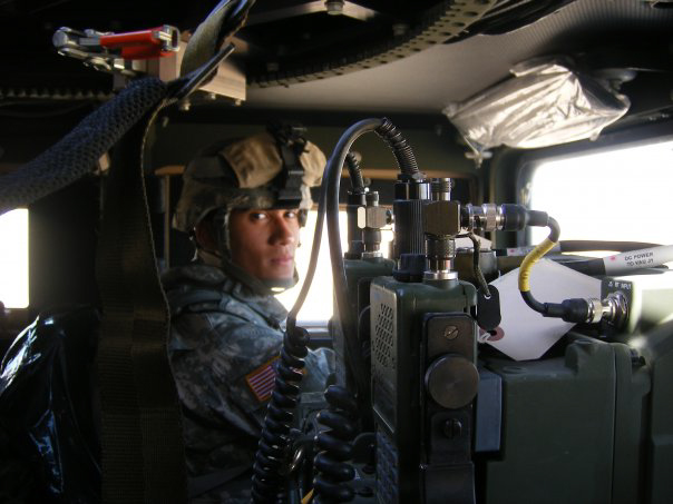 Steve Baskis in his Army Uniform sits behind communications equipment in a Humvee