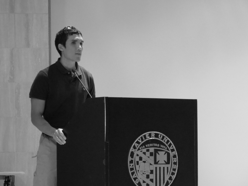 Steve Baskis stands behind a podium while speaking to St Xavier University